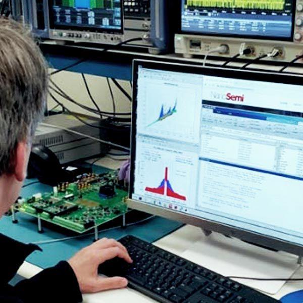 NanoSemi engineer working on computer. Rack of lab equipment in background.