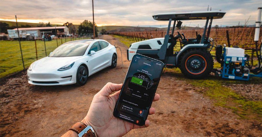 In background: Tractor is charging an electric car. In foreground: Person holding a cell phone displaying the vehicle's charging status.